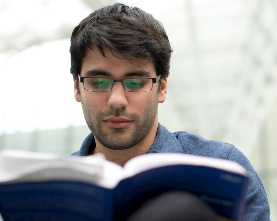 Male student reading a textbook